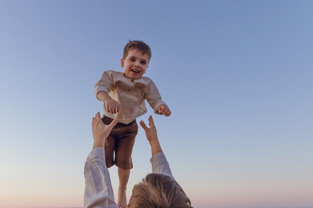 Il divertimento del padre vomita il figlio in aria. bambino gioioso felice.