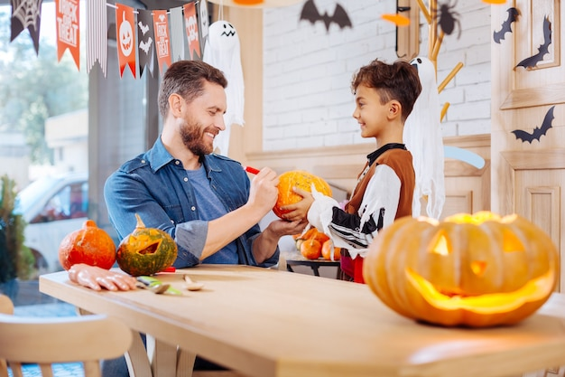 Padre che aiuta. padre barbuto premuroso che si sente memorabile mentre aiuta suo figlio che indossa la zucca dipinta in costume di halloween