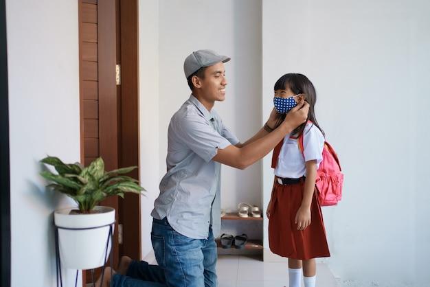 Padre che aiuta sua figlia a indossare una maschera prima di andare a scuola la mattina per prevenire un virus covid 19