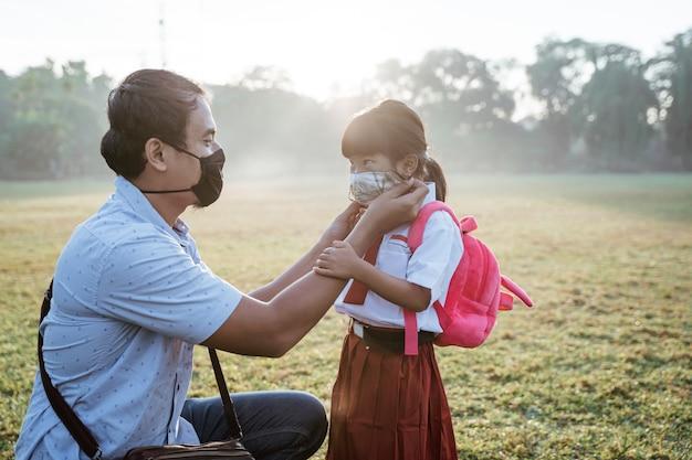 Padre che aiuta sua figlia a indossare una maschera prima di andare a scuola