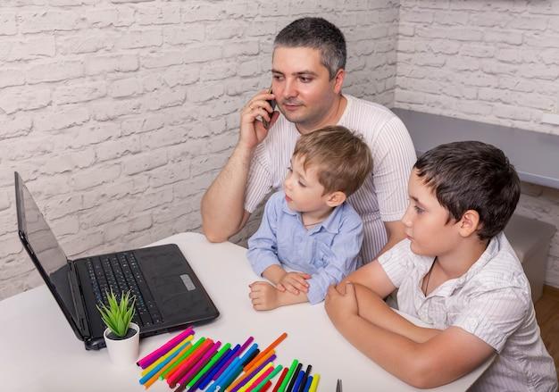 Padre che aiuta i suoi figli a fare i compiti online