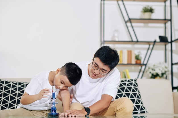 Padre che aiuta il figlio preadolescente con i compiti di biologia e spiega come usare il microscopio