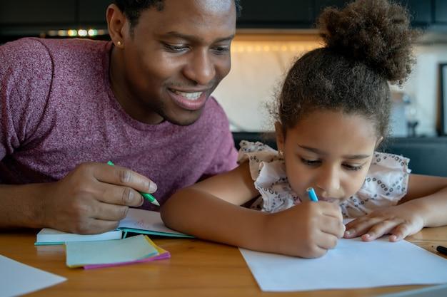 Padre che aiuta e sostiene sua figlia con l'istruzione domestica mentre è a casa.