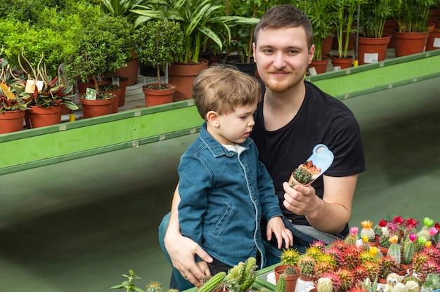 Padre e il suo bambino in un negozio di piante guardando i cactus. giardinaggio in serra. giardino botanico, floricoltura
