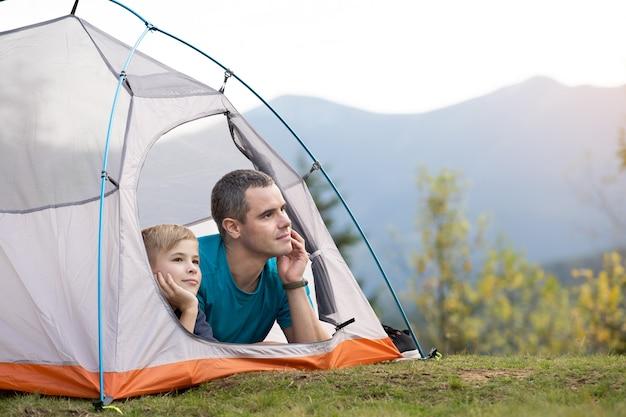 Padre e suo figlio figlio che fanno un'escursione insieme nelle montagne estive