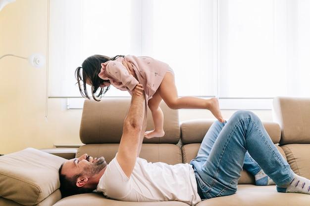 Un padre e sua figlia ridono e giocano sul divano di casa