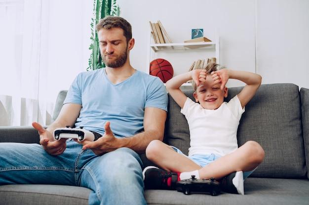Padre e suo figlio piccolo che giocano insieme ai videogiochi sul divano di casa