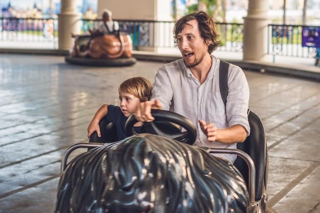 Padre e figlio che fanno un giro nell'autoscontro al parco di divertimenti.