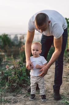 Padre e figlio che giocano e si abbracciano all'aperto.