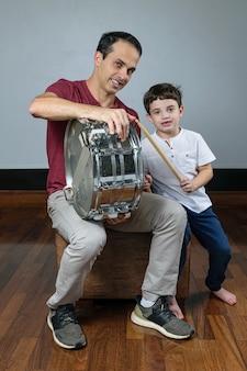 Padre e suo figlio con un tamburo e bacchette