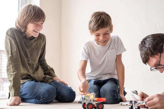 Padre e figli trascorrono del tempo insieme, divertendosi a costruire auto robot a casa seduti sul tappeto
