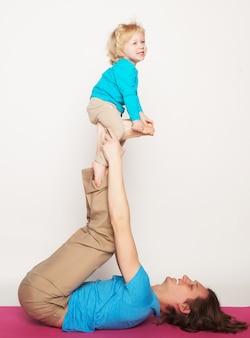Padre che tiene in piedi il figlioletto, yoga, famiglia felice
