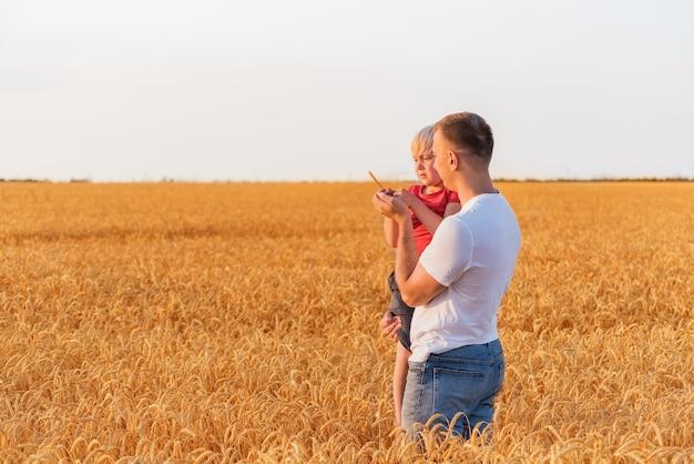 Padre che tiene il figlio tra le braccia sul campo di sfondo di grano maturo. weekend in campagna.