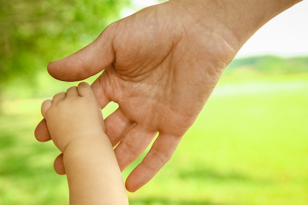 Un padre tiene la mano di un bambino piccolo nel parco sullo sfondo vacanza natura