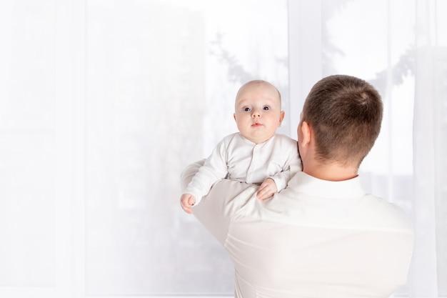 Un padre tiene un neonato sulla spalla a casa vicino alla finestra, il concetto di una famiglia felice e amorevole, la festa del papà