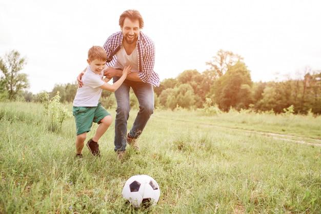 Padre sta giocando a calcio con suo figlio. stanno correndo giù per il prato. il ragazzo sta abbracciando suo padre e guardando la palla. l'uomo sta facendo la stessa cosa.