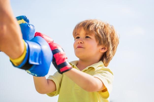 Il padre sta allenando il figlio di boxe. ragazzino che fa esercizio di boxe con il nonno. ragazzino sportivo all'addestramento di boxe con l'allenatore. uomo di sport coaching boxe ragazzino in guantoni da boxe rossi.
