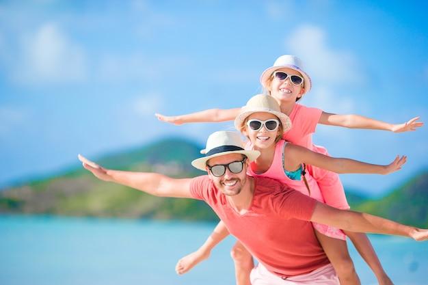 Padre e bambini che godono della vacanza tropicale di estate della spiaggia Foto Premium