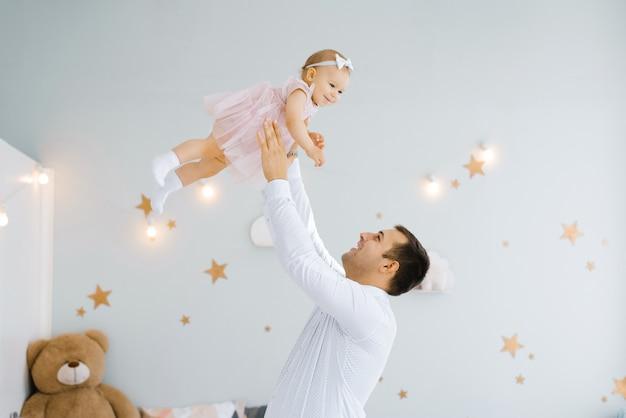 Neonata di sollevamento del padre. il padre felice prende e lancia il suo sollevamento di un bambino piccolo. atmosfera di casa, famiglia felice che ride bambino