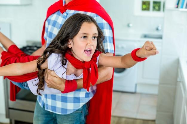 Padre ragazza di sollevamento in costume da supereroe