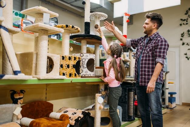 Padre e figlia piccola che acquistano forniture per il gatto nel negozio di animali. la famiglia sceglie gli accessori per il cane nel negozio di animali