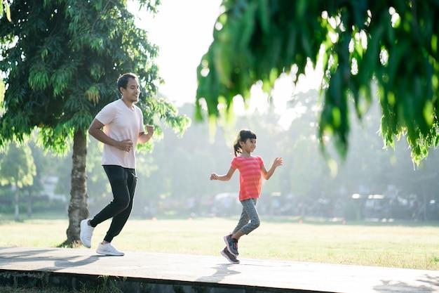 Padre e figlia fanno esercizi nello stile di vita sano all'aperto della famiglia con bambino with