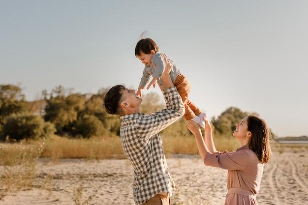 Padre madre che tiene bambino figlio sulle mani e andare insieme