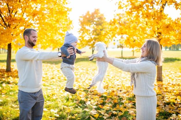 Padre e madre che tengono cucciolo e bambino nelle loro mani.