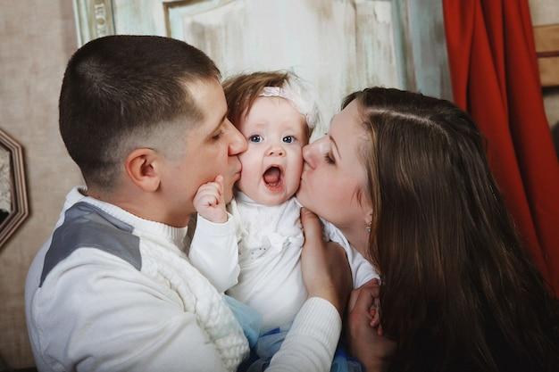 Padre e madre baciano il bambino. concetto di famiglia.