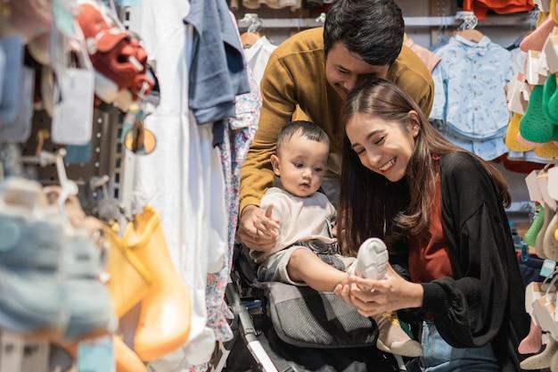Padre e madre fanno la spesa al baby shop con il figlio nel passeggino
