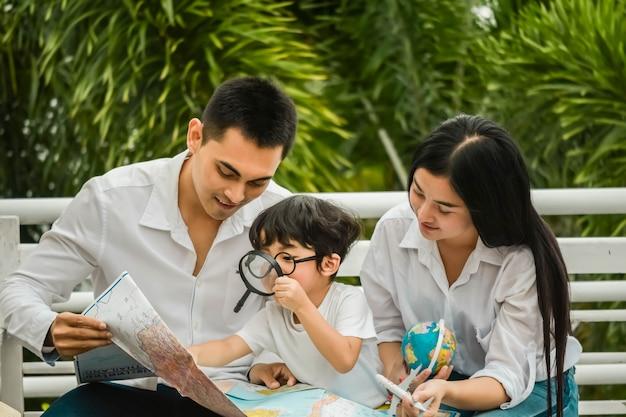 Padre, madre e figlio con in mano una mappa per il viaggio di famiglia