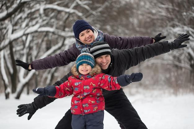 Padre, madre e figlio che giocano con le palle di neve in inverno