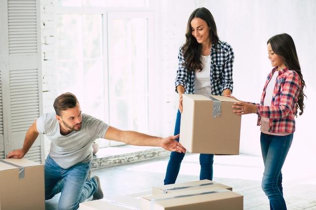 Padre, madre e la loro graziosa figlia adolescente tengono in mano una scatola con le loro cose nel nuovo appartamento