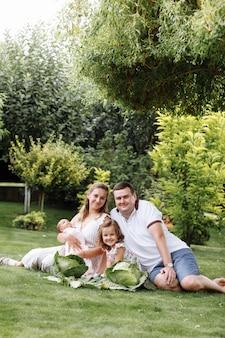 Padre, madre e due bambini, neonata e piccola figlia sull'erba con i cavoli