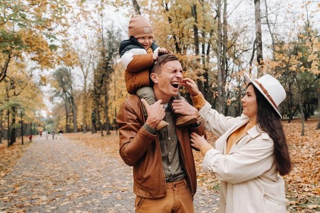 Padre e madre con il figlio che camminano nel parco di autunno. una famiglia cammina nell'autunno dorato in un parco naturale.