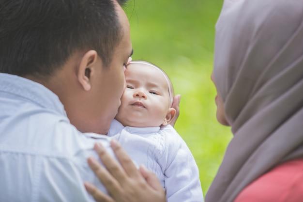 Padre e madre con il loro neonato nel parco.