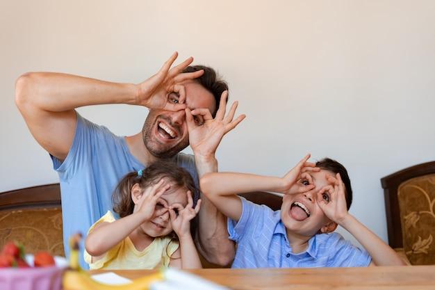 Un padre o una tata si diverte con due bambini piccoli, una femmina e un maschio, ridono e mostrano smorfie divertenti con le dita vicino agli occhi come se fossero degli occhiali.