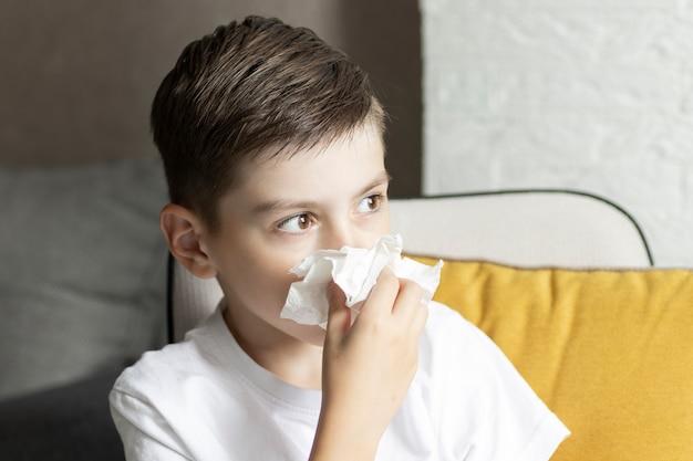 Un padre in congedo di paternità che si prende cura del figlio piccolo in casa, soffiandosi il naso.