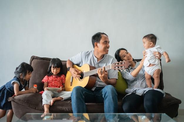 Padre a suonare la chitarra sul divano con la sua famiglia