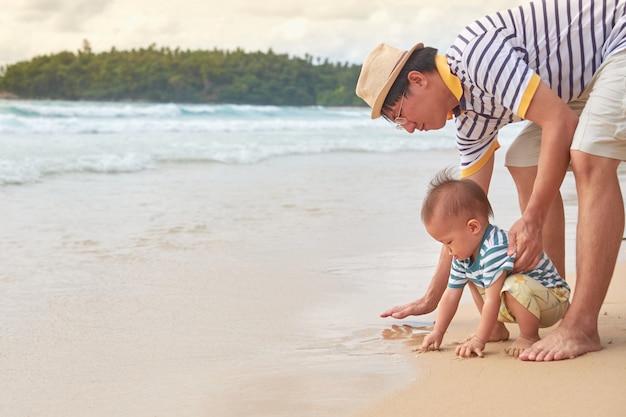 Padre giocando a sabbia con cute asian 18 mesi di età bambino ragazzo bambino sulla spiaggia di sabbia bianca, vacanze estive in spiaggia con bambini, gioco sensoriale con il concetto di sabbia