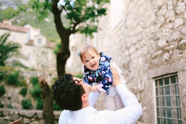 Il padre ha sollevato la sua piccola figlia ridente tra le sue braccia sullo sfondo del cortile di an