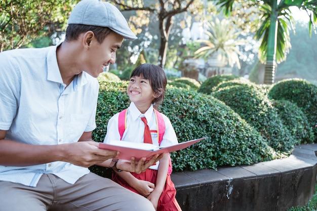 Padre che legge un libro a sua figlia nel parco