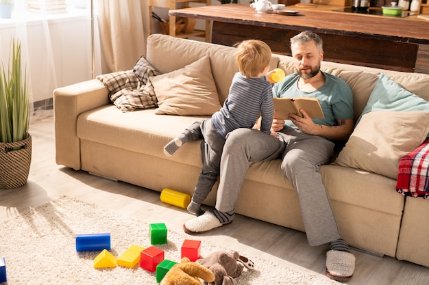 Padre che legge il libro mentre il figlio chiede di giocare con lui