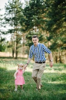 Il padre corre con una figlia e le tiene la mano sulla natura durante le vacanze estive. papà e ragazza che camminano e giocano nel parco all'ora del tramonto. concetto di famiglia amichevole. avvicinamento.