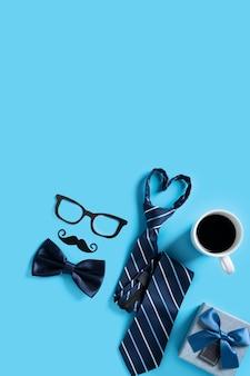 Concetto di design di sfondo per la festa del papà. vista dall'alto delle idee di layout della decorazione della carta a colori con confezione regalo su sfondo blu della tavola con spazio di copia.