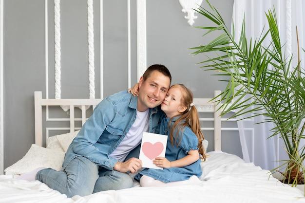 Concetto della festa del papà, una figlia ragazza regala al suo amato padre un biglietto d'auguri per la festa del papà