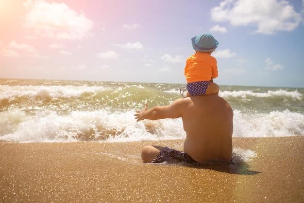 Festa del papà. papà con un bambino sulle spalle in attesa di un'onda seduto sulla sabbia.