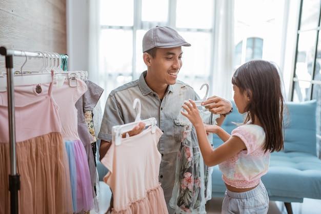 Padre che fa shopping con la sua bambina in una piccola boutique