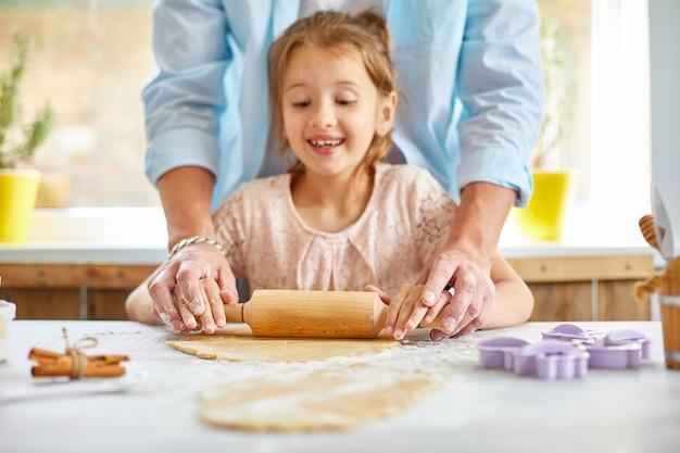 Padre che mostra alla sua piccola figlia come stendere la pasta per i biscotti, cuocere in cucina, cucinare in famiglia a casa.