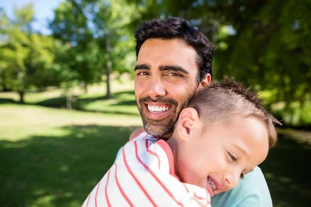 Generi sorridere mentre abbraccia suo figlio in parco